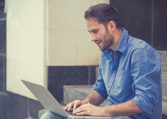 Handsome young happy businessman working on laptop outdoors