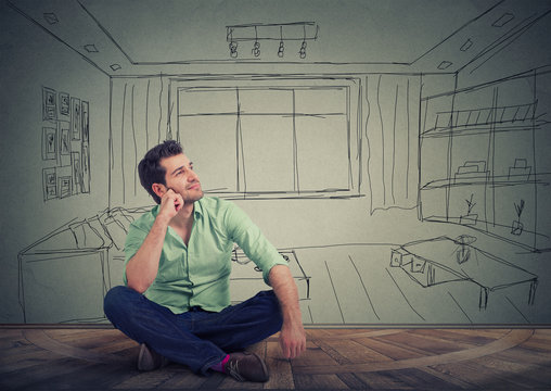 Dreaming man isolated over drawn living room background.