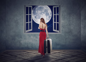 Beautiful woman in red dress walking to opened window with moon