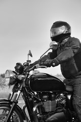 Black and white image of side of motorbike with rider in leathers.