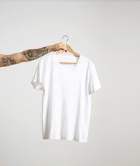 Tattooed biker hand holds hang with blank white t-shirt from premium thin cotton, isolated on white mockup