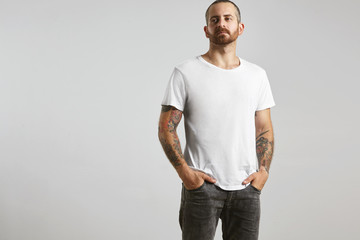 Attractive brutal tattooed bearded guy poses in black jeans and blank white t-shirt from premium thin summer cotton, isolated on white mockup