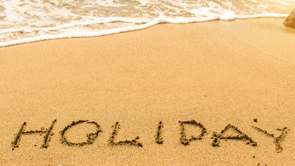 Holiday - hand-written on the sand in line of the sea surf.