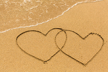 Two of hearts drawn on a sandy beach in the line of sea surf.