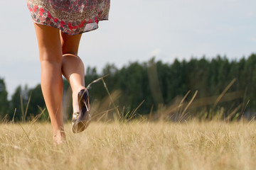 Portrait of barefoot woman in long red dress walking on the road in the green field in summer