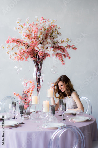 Smiling Bride Sitting By The Table And Wedding Decorations For