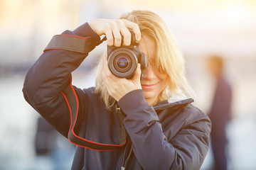 Young woman using a camera to take photo outdoor.