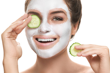 Woman with facial mask and cucumber slices in her hands