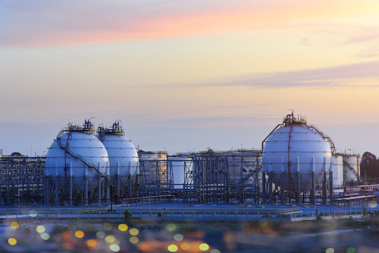 A large oil-refinery plant with Liquefied Natural Gas (LNG) storage tanks and sunset.