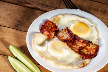 Fried eggs with bacon and sliced cucumber