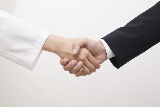 握手する医者とビジネスマン