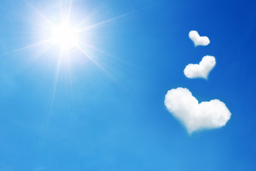 three heart shaped cloud on blue sky with sunshine