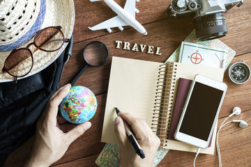 Outfits and accessories of traveler on wooden background