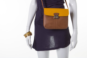 Brownish-yellow leather bag on a mannequin.