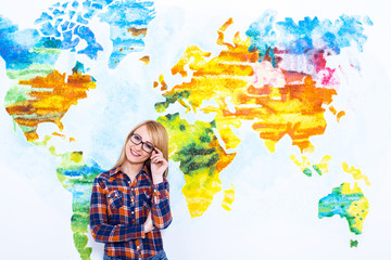 Confident in her future. Cheerful young women adjust her glasses and smiling while standing against map of the world.