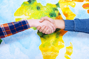 Good job! Close-up of two people shaking hands while in front of wall painted like a map of Africa.