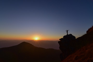 Man standing on the rock during sunset at the mountain.