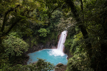Turquois volcanic waterfall in the rainforest of Costa Rica