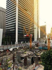 Construction site with workers, meterials and cranes for building tower