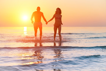 Silhouette of young fitness couple walking inside the water at sunrise