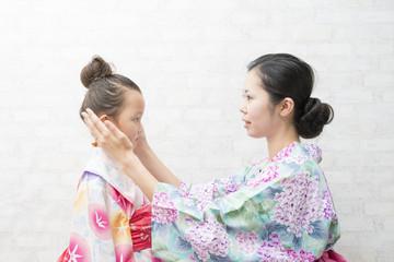 浴衣を着て髪を整える親子