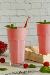 Raspberry milkshake with mint and  straws.