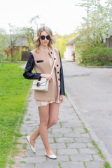 beautiful sexy girl with full lips walks in sunglasses in a coat with a handbag through the city streets