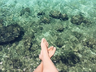 relax feet above cystal clear water
