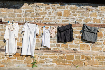 Underwear and clothing hanging drying on ancient stown wall