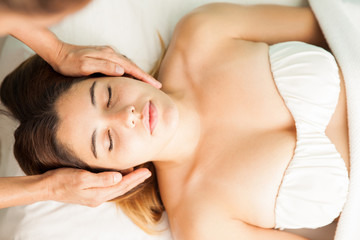 Woman receiving reiki therapy at a spa