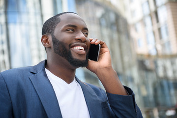 Cheerful African businessman using telephone for communication