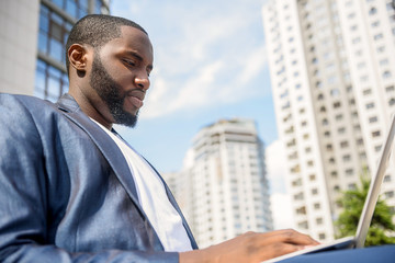 Serious African businessman working on laptop outdoors