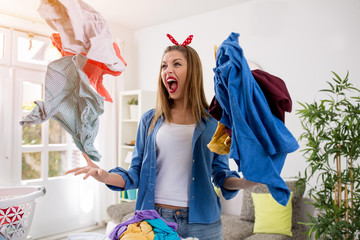 Aggressive frustrated woman throws laundry in the air