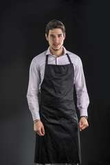 Young chef or waiter posing, wearing black apron and shirt, on dark background