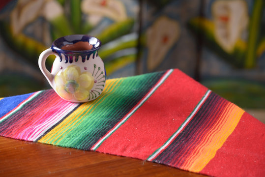 Empty wooden table over wood background with mexican coffee mug copy space