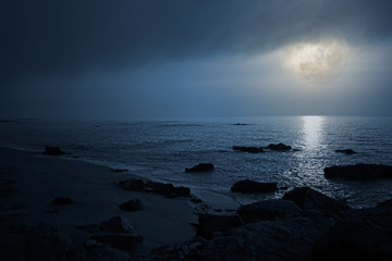 Empty seaside in a cloudy full moon night