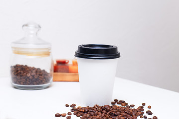 paper cup with coffee and coffee beans