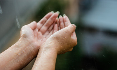 Hands catching clean falling rain drops close up. Environmental and healthcare concept