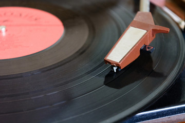 ancient player of vinyl records with a plate and the sound receiver macro isolate a white background