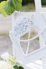 beautiful white frame with beads for a photo hanging on the stairs