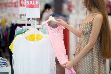 Long-haired young pretty woman in shopping centre store choosing clothes looking at pink lace dress standing sideways. Sales, shopping, fashion concept. Close-up of torso
