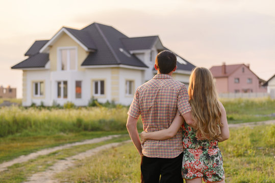 rear view of young couple looking at their new house