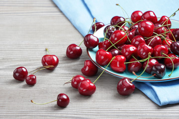 Ceramic plate with organic cherry at old wooden table. Close up, high resolution product. Harvest Concept