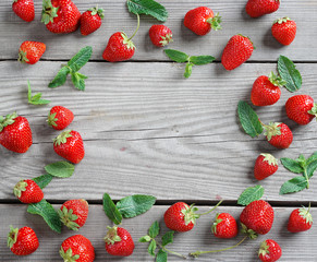 Frame from strawberry and mint leaf on wooden background. Close up, top view, high resolution product.