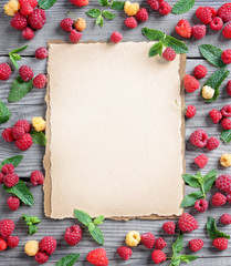 Fram from raspberries and mint leaf with beige background in the center. Close up, top view, high resolution product.