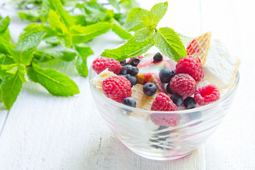 Ice cream with berries and mint. Dessert. White wood background, old board.