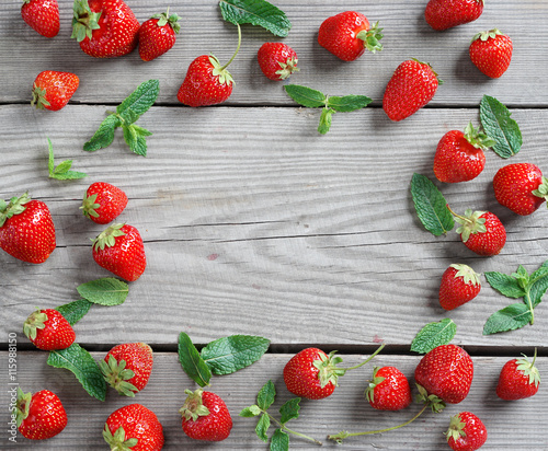Frame from strawberry and mint leaf on wooden background. Close up ...