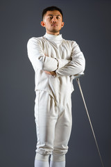 Fencing athlete posing with a sword or epee on gray background
