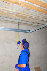 Contractor with measuring tape Installing Garage Door Post Rail and Spring Installation and Garage Ceiling. Garage Door Installation Step by Step.