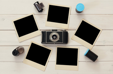 empty instant photographs next to old camera and film rolls